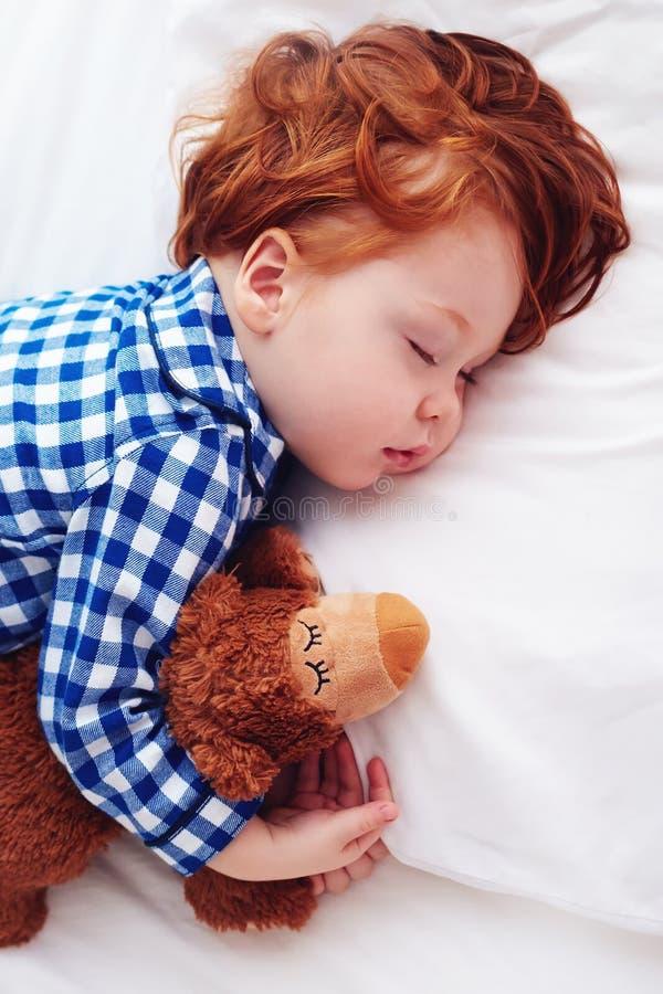 Bebé adorable del niño del pelirrojo que duerme con el juguete de la felpa en franela imagen de archivo libre de regalías
