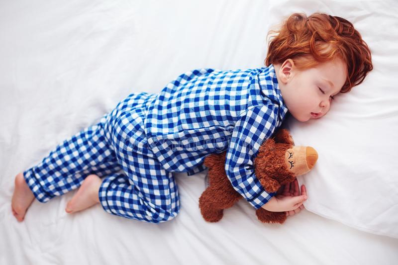 Bebé adorable del niño del pelirrojo que duerme con el juguete de la felpa en pijamas de la franela fotos de archivo libres de regalías