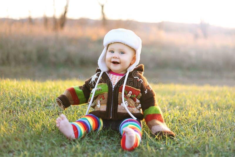 Bebé adorable en sombrero y suéter del invierno que ríe afuera foto de archivo libre de regalías