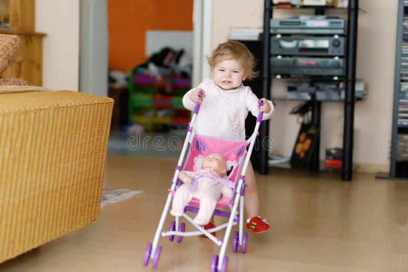 Bebé adorable lindo que hace los primeros pasos con el carro de la muñeca fotografía de archivo libre de regalías