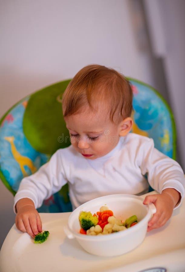 Bebé adorable que come el bróculi en casa imagen de archivo
