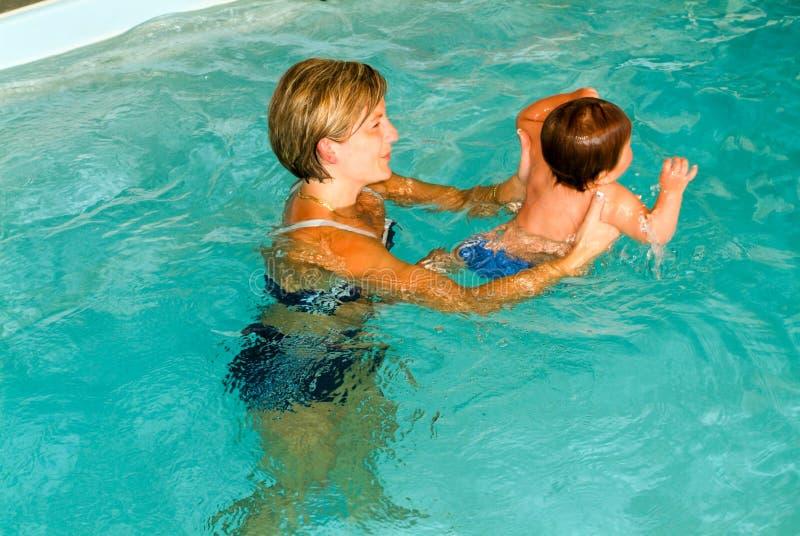 Bebé adorable que disfruta de nadar en una piscina con su madre fotos de archivo