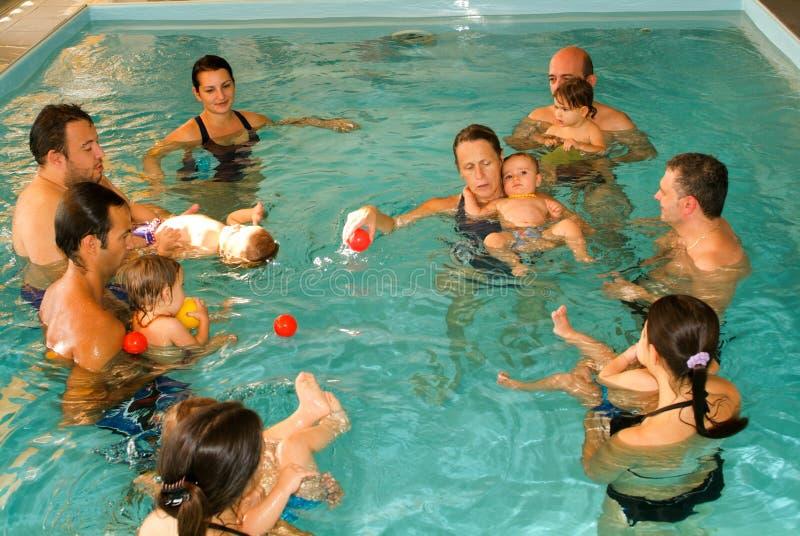 Bebé adorable que disfruta de nadar en una piscina con su madre foto de archivo