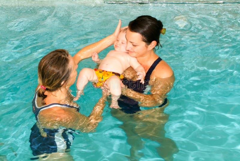 Bebé adorable que disfruta de nadar en una piscina con su madre fotografía de archivo libre de regalías