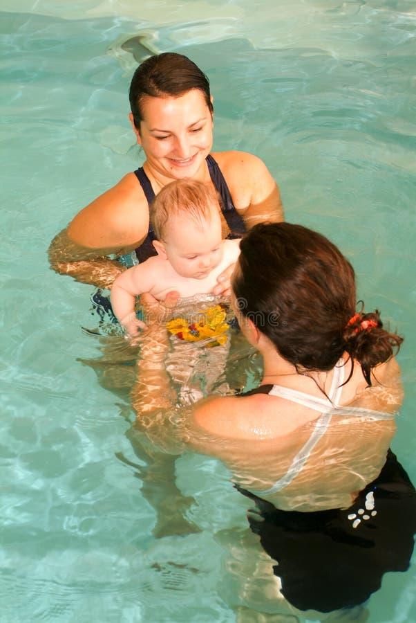 Bebé adorable que disfruta de nadar en una piscina con su madre imagenes de archivo