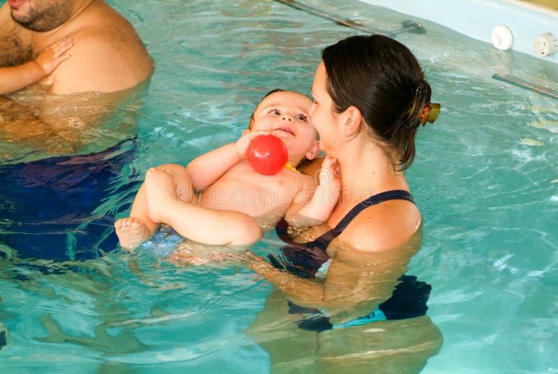 Bebé adorable que disfruta de nadar en una piscina con su madre imagen de archivo