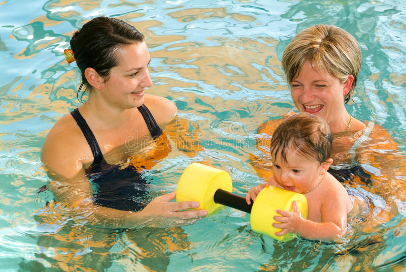 Bebé adorable que disfruta de nadar en una piscina con su madre fotografía de archivo