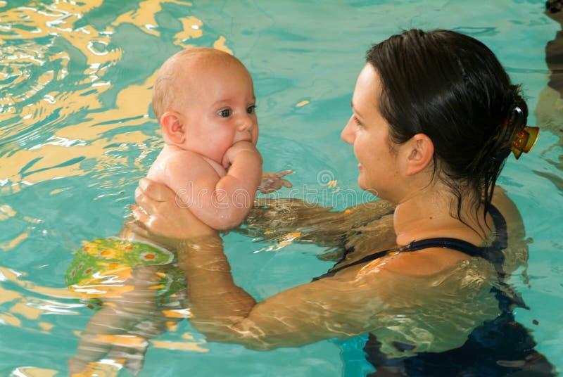 Bebé adorable que disfruta de nadar en una piscina con su madre foto de archivo libre de regalías