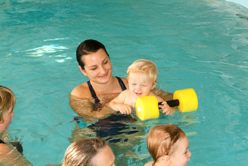 Bebé adorable que disfruta de nadar en una piscina con su madre imagen de archivo libre de regalías