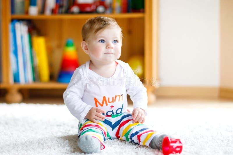 Bebé adorable que juega con los juguetes educativos en cuarto de niños Niño sano feliz que se divierte con diversos juguetes colo foto de archivo