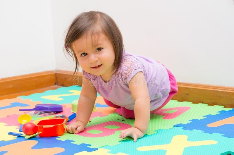 Bebé adorable que juega en piso foto de archivo