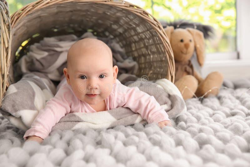 Bebé adorable que miente en la tela escocesa suave cerca de cesta fotos de archivo libres de regalías