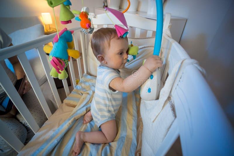 Bebé adorable que se coloca en pesebre y que juega con el carrusel del juguete imagenes de archivo