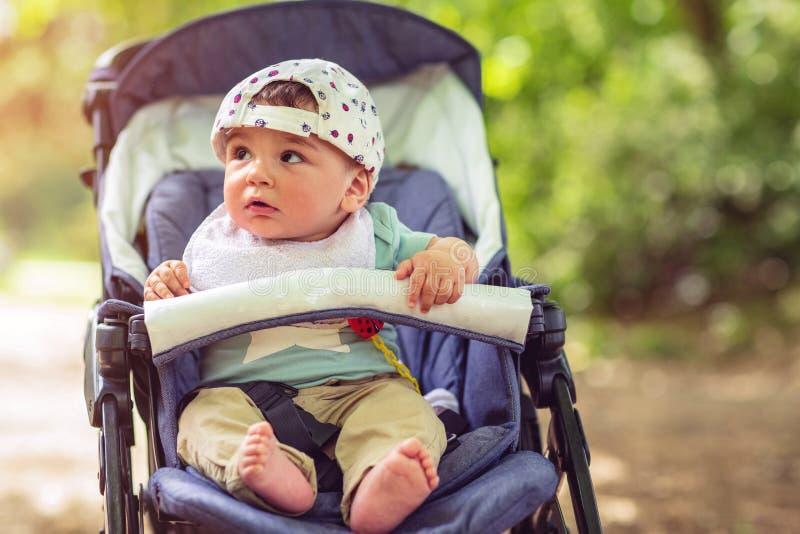 Bebé adorable que se sienta en cochecito y que sonríe feliz fotos de archivo libres de regalías