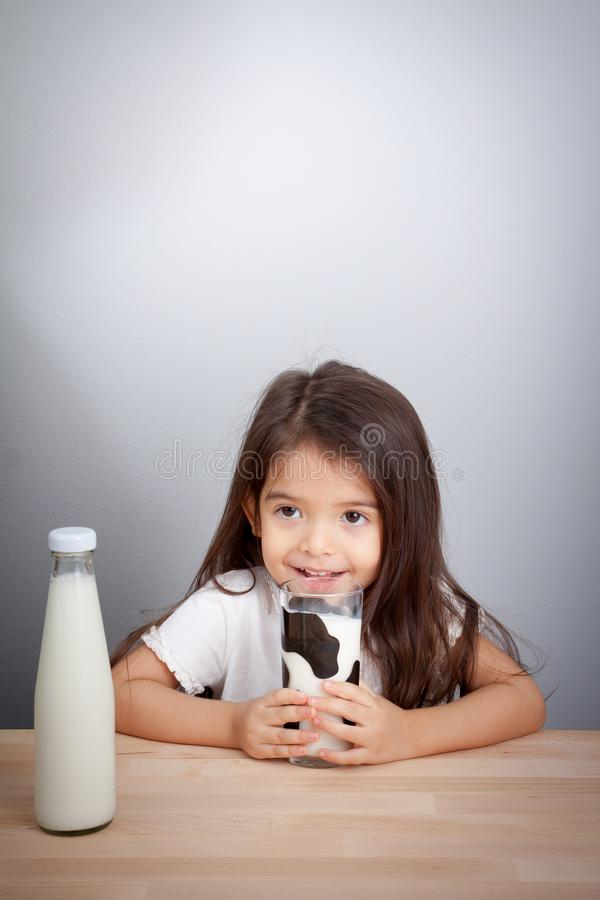 Bebé adorable que sostiene el vidrio de leche y de leche de consumo fotografía de archivo libre de regalías