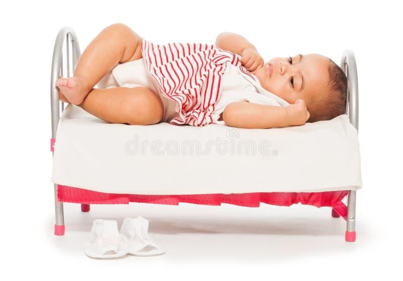 Bebé africano en vestido rayado en la pequeña cama foto de archivo libre de regalías
