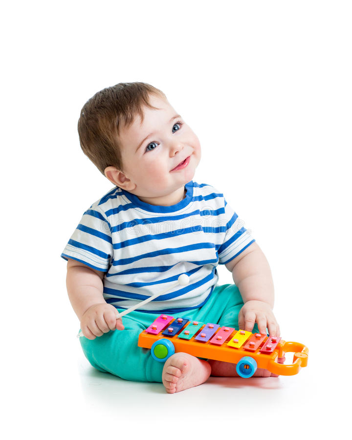 Bebé agradable que juega con los juguetes musicales foto de archivo