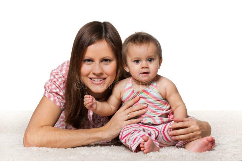 Bebé alegre con la madre sonriente foto de archivo