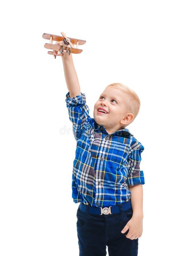 Bebé alegre que juega con un aeroplano del juguete que lo levanta alto sobre su cabeza Aislado en blanco imágenes de archivo libres de regalías