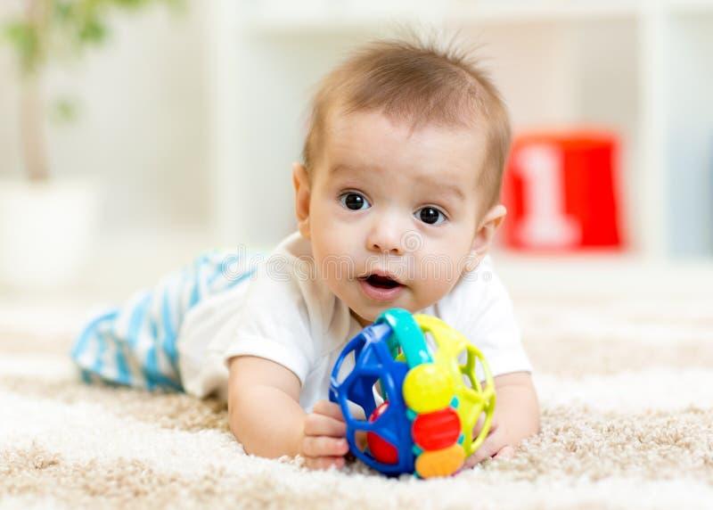 Bebé alegre que miente en el piso en sitio del cuarto de niños fotos de archivo libres de regalías