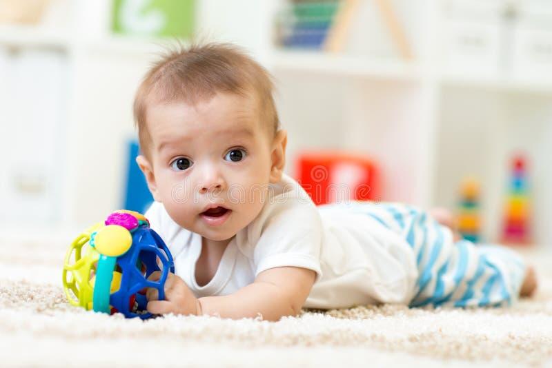 Bebé alegre que miente en la alfombra en sitio del cuarto de niños fotos de archivo libres de regalías