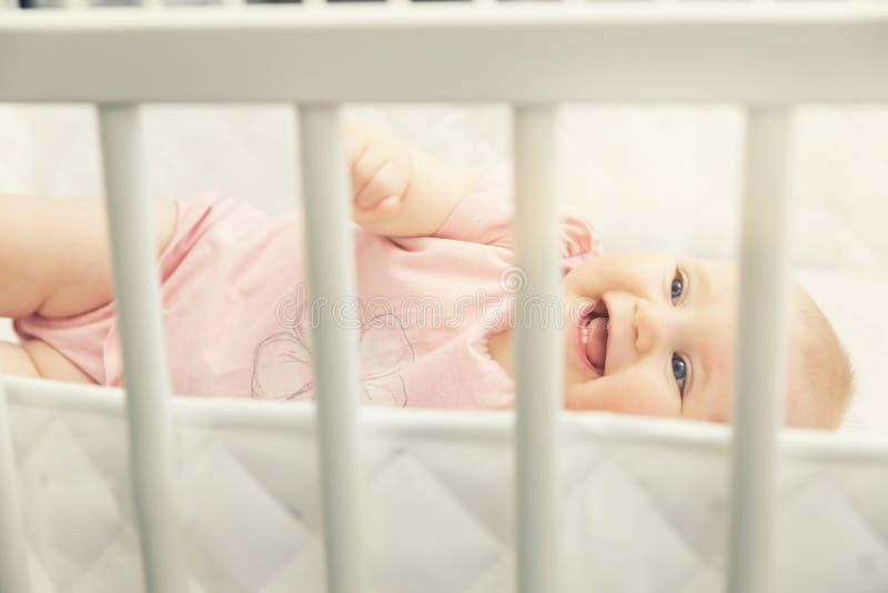Bebé alegre que miente en pesebre en casa foto de archivo
