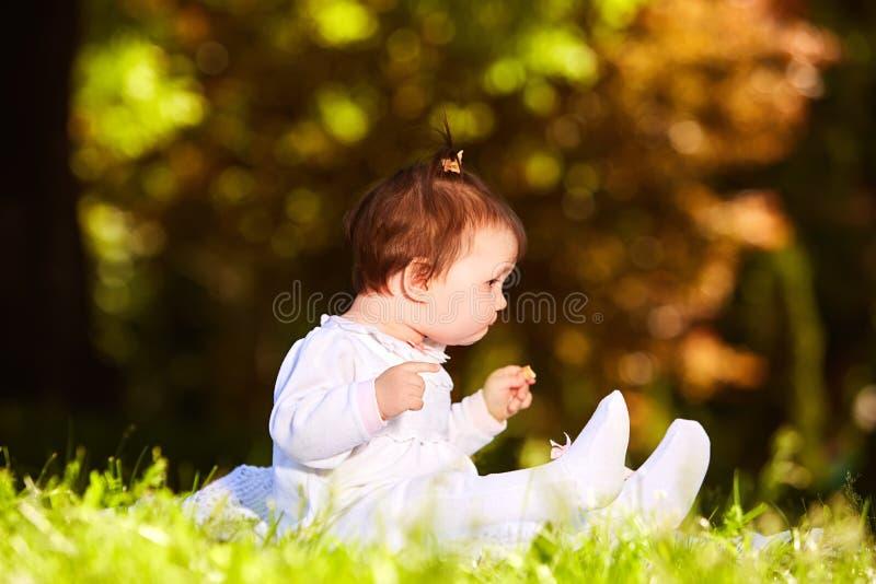 Bebé alegre que se sienta en la hierba verde en el parque de la ciudad en el día de verano imagen de archivo