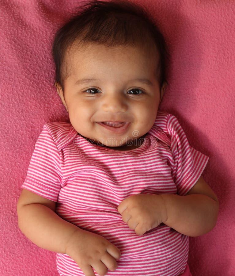 Bebé asiático de riso em panos cor-de-rosa imagem de stock