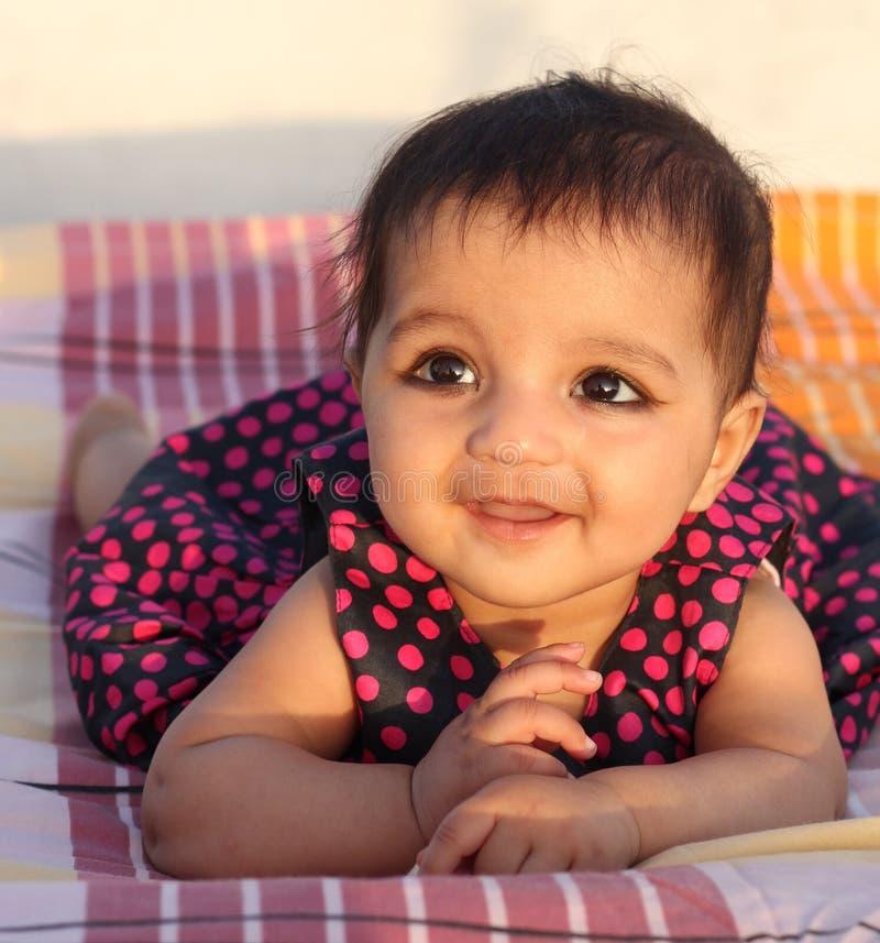 Bebé asiático de sorriso que olha o visor fotos de stock