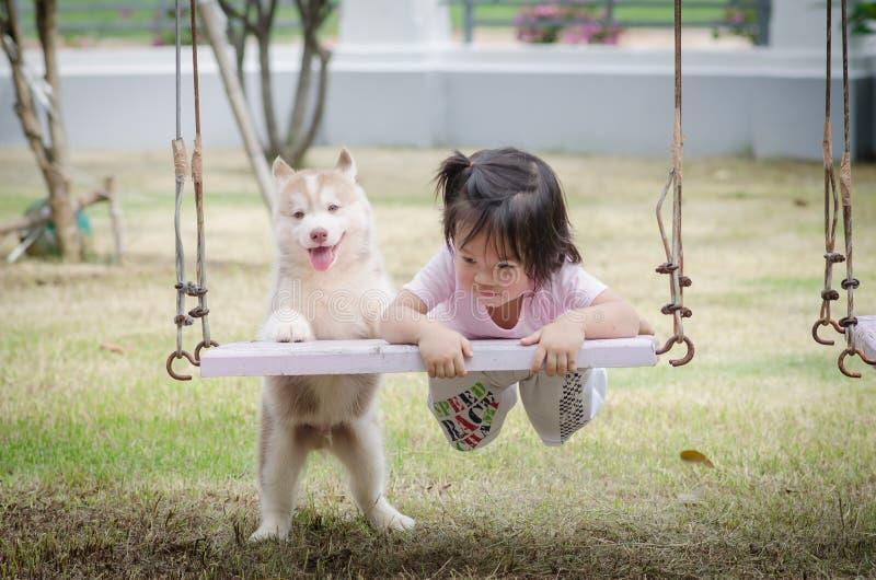Bebé asiático del bebé en el oscilación con el perrito fotografía de archivo libre de regalías