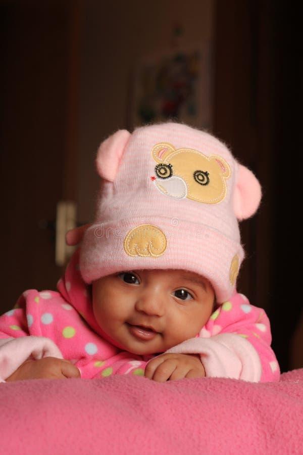 Bebé asiático inocente no tampão cor-de-rosa do inverno fotografia de stock