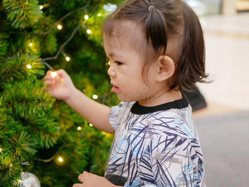 Bebé asiático inocente que lleva a cabo encendido una luz de la secuencia en un árbol de navidad sin miedo de un riesgo de ser el imágenes de archivo libres de regalías