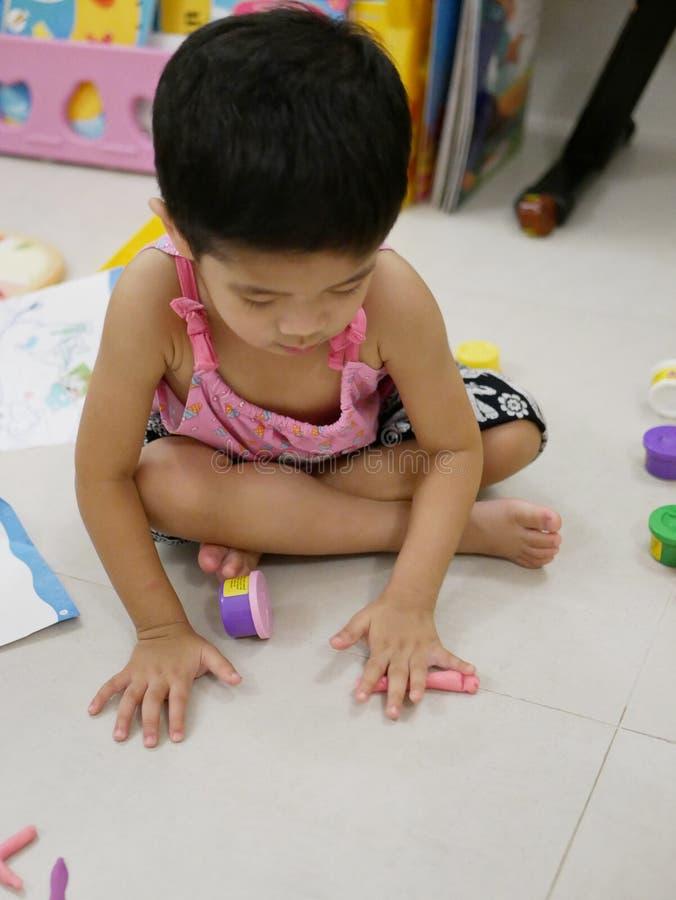 Bebé asiático que juega la pasta del juego en el piso en casa fotografía de archivo libre de regalías