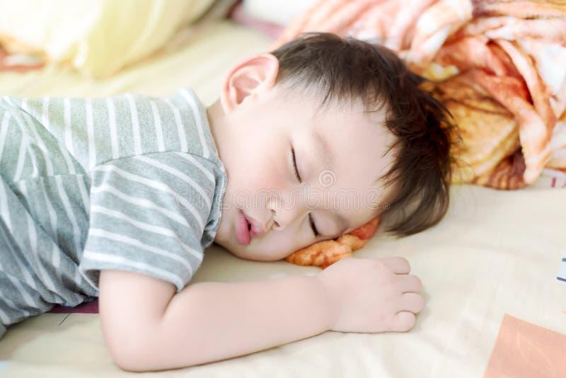 Bebé asiático que pone en el sofá imagenes de archivo