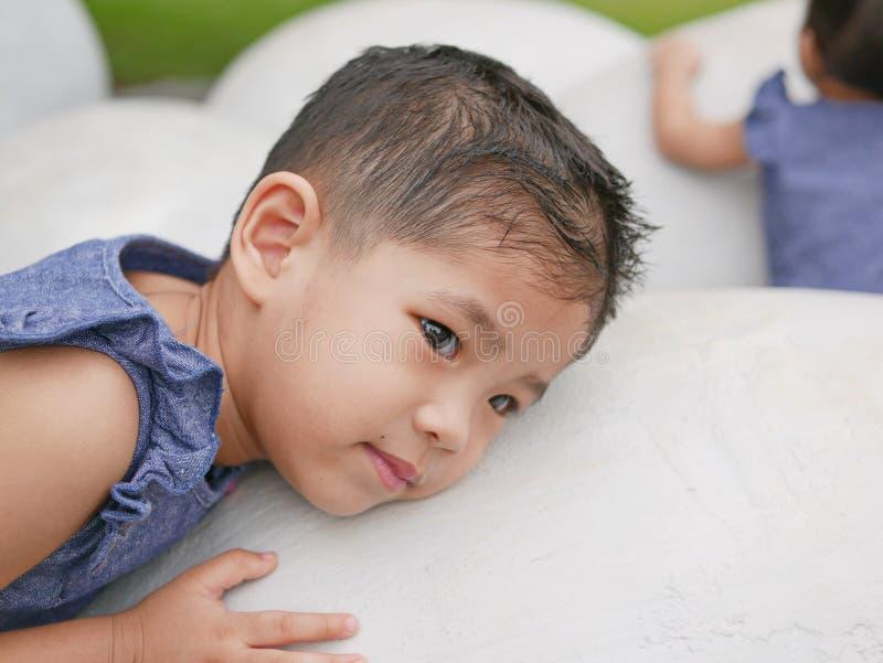 Bebé asiático que pone su oído contra un huevo de dinosaurio imagenes de archivo