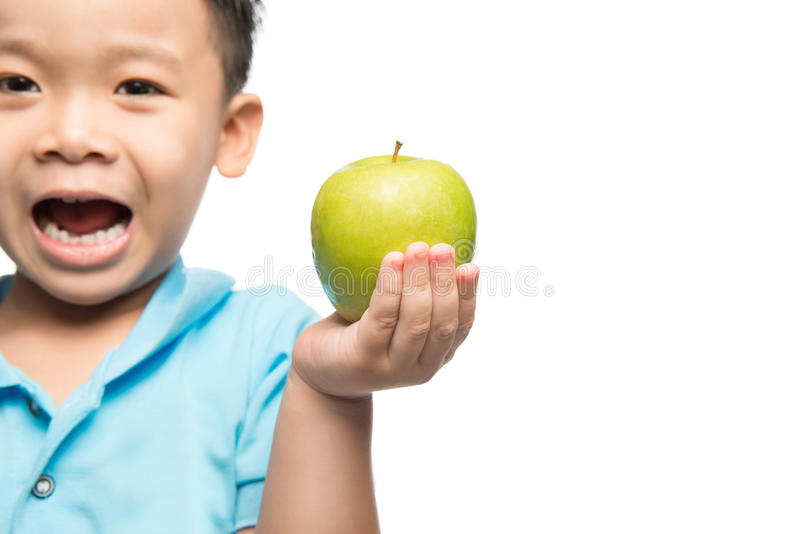 Bebé asiático que sostiene y que come la manzana roja, aislada en blanco foto de archivo