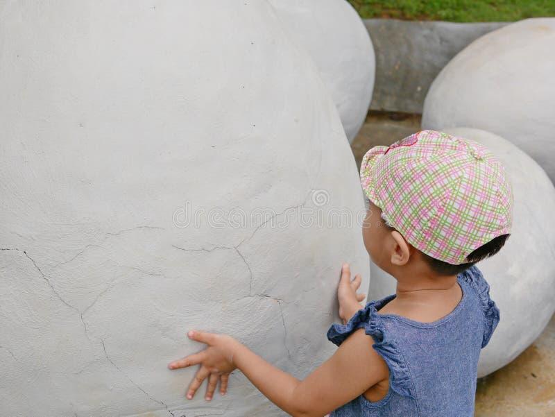 Bebé asiático que toca un huevo de dinosaurio para explorar si ella siente cualquier cosa dentro imagen de archivo libre de regalías