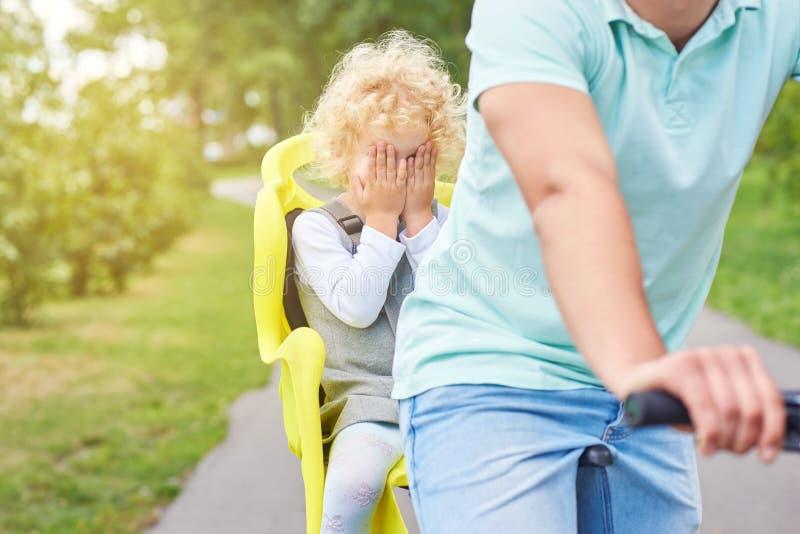Bebé asustado en un asiento de la bici en una bicicleta fotografía de archivo libre de regalías
