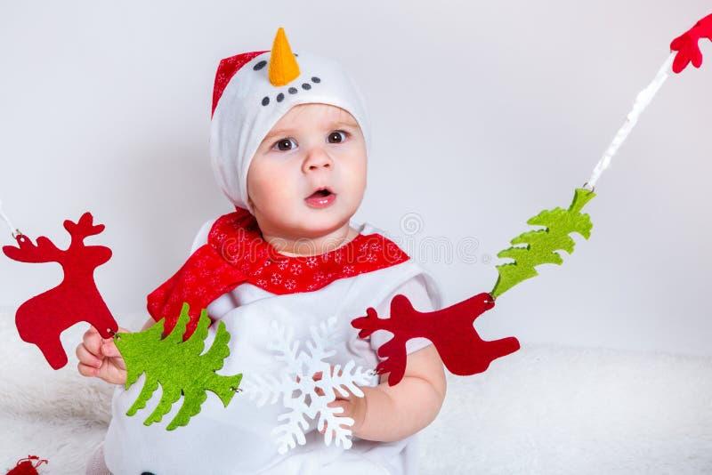 Bebé atractivo sorprendente en el traje de la Navidad que se divierte Niña del retrato del primer en traje del muñeco de nieve fotografía de archivo