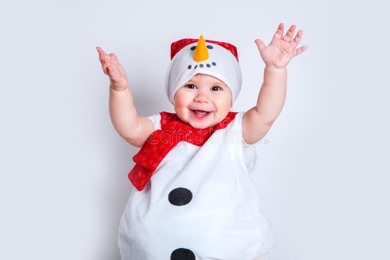 Bebé atractivo sorprendente en el traje de la Navidad que se divierte Niña del retrato del primer en traje del muñeco de nieve fotografía de archivo libre de regalías