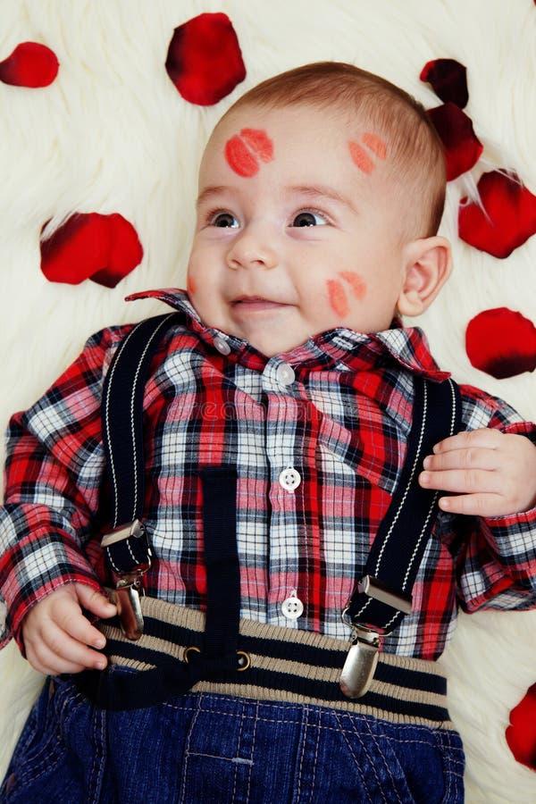 Bebé bonito de sorriso com batom em sua face fotografia de stock royalty free