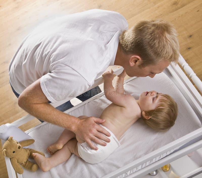 Bebé cambiante del hombre foto de archivo libre de regalías