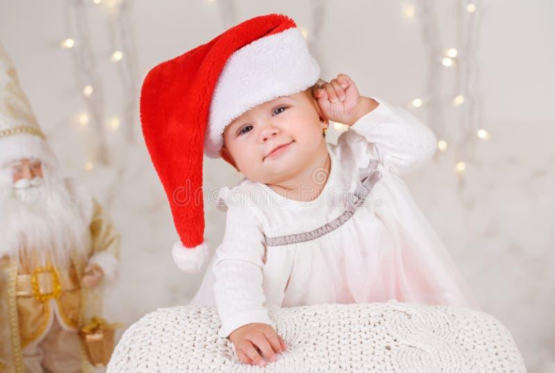 Bebé caucásico con los ojos azules que llevan el sombrero de Papá Noel que celebra día de fiesta de la Navidad o del Año Nuevo fotos de archivo libres de regalías