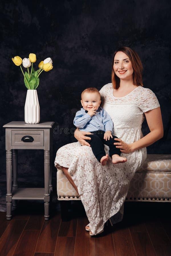 Bebé caucásico del padre femenino y del hijo que se sienta junto en el sofá dentro Día de fiesta feliz del día de la madre imágenes de archivo libres de regalías