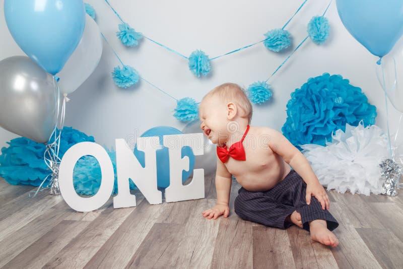 Bebé caucásico en pantalones oscuros y corbata de lazo azul que celebra su primer cumpleaños con las letras una y los globos foto de archivo