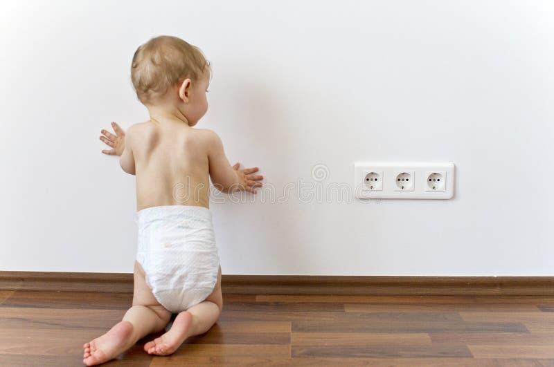 Bebé cerca de los enchufes eléctricos imagenes de archivo