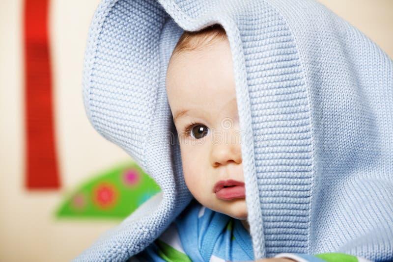 Bebé com o cobertor azul na cabeça. imagens de stock