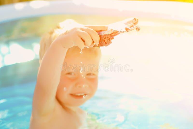 Bebé con el avión del juguete en piscina Niño pequeño que aprende nadar en piscina al aire libre imagen de archivo libre de regalías