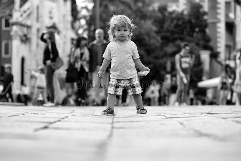 Bebé con el bollo en el pavimento imagen de archivo