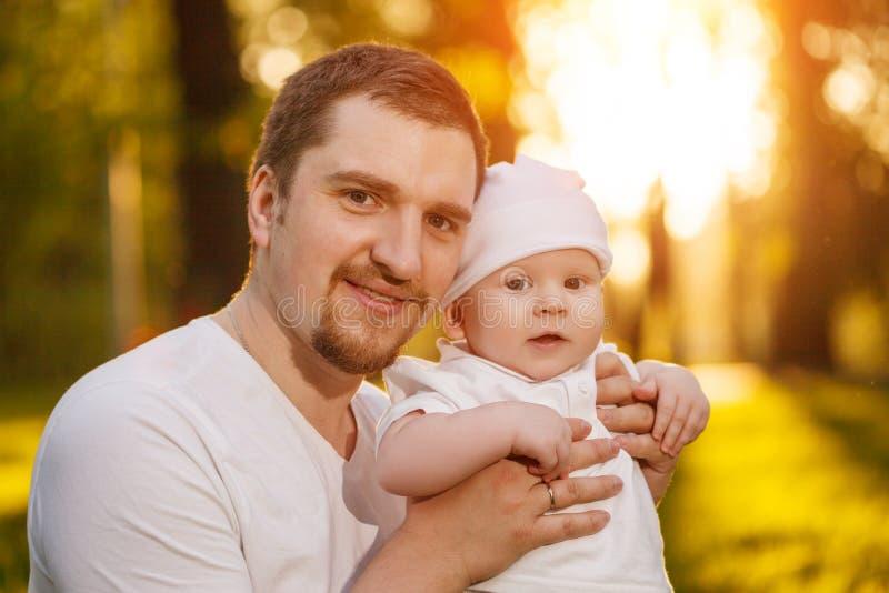 Bebé con el faher en el parque en los rayos de la puesta del sol Niño en la naturaleza al aire libre Contraluz Escena de la famil imágenes de archivo libres de regalías